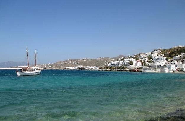 Barco de pesca branco e pequena cidade entre o céu azul e mar azul, ilha de mykonos da grécia