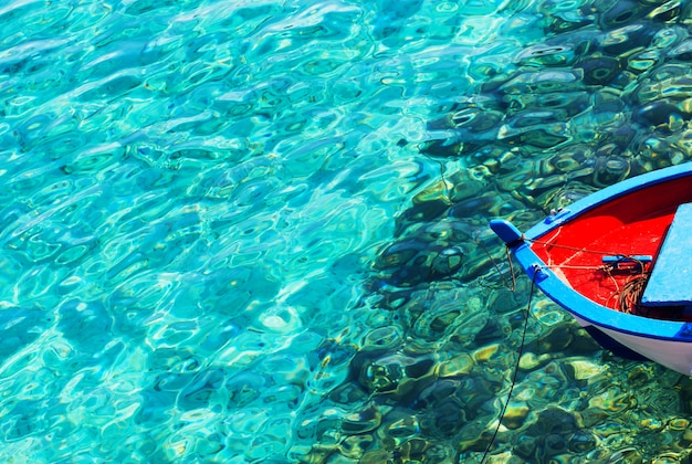 Barco de pesca colorido em uma água azul desobstruída em um dia ensolarado. abstrato com espaço de cópia.