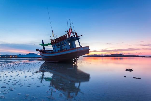 Barco de pesca com o nascer do sol no mar com reflexo e nuvem na praia de rawai