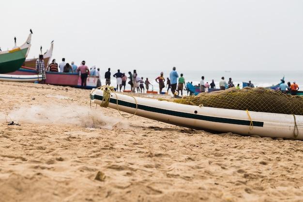 Barco de pesca com rede e pescadores na parte traseira que espera uma captura.
