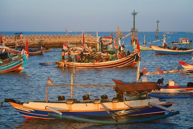 Barco de pesca de madeira artesanal colorido de bali no porto na praia de jimbaran, bali