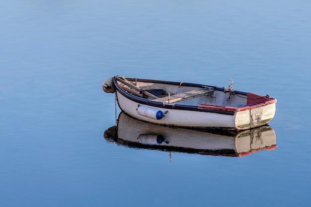 Barco de pesca de madeira branco em um mar calmo