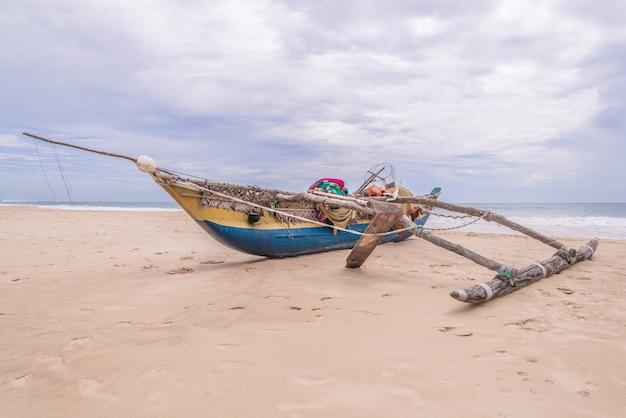 Barco de pesca de madeira com equipamento de pesca na paisagem marítima.
