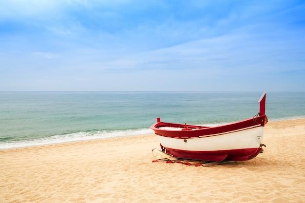 Barco de pesca de madeira em uma praia arenosa