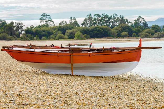 Barco de pesca de madeira laranja em uma praia de ilha deserta