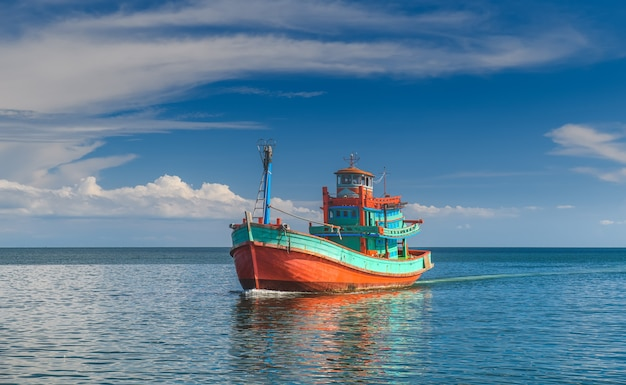 Barco de pesca de madeira no mar com luz solar ao ar livre e céu nublado
