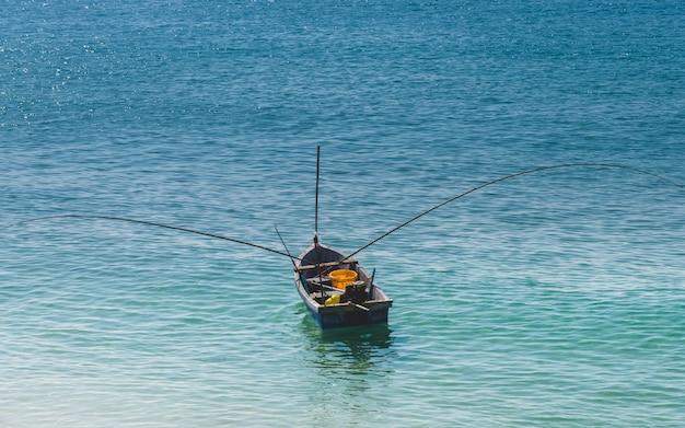 Barco de pesca de madeira pequeno no mar azul.