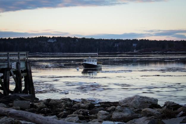 Barco de pesca de tamanho médio, cruzando a costa no mar, perto de uma praia rochosa antes do anoitecer