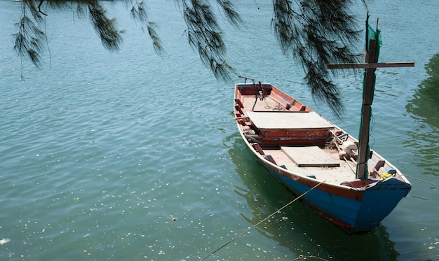 Barco de pesca do pescador ancorado no cais sob pinheiro com água do mar verde azul natural