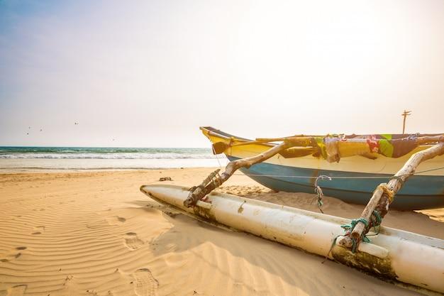 Barco de pesca e praia arenosa no ceilão. areias do sri lanka, oceano índico