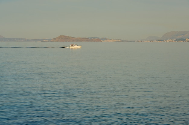 Barco de pesca em alto mar com a costa de creta