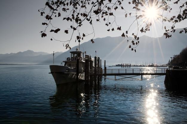 Barco de pesca em um lago alpino com belos raios de sol na suíça