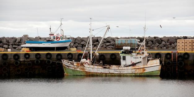 Barco de pesca enferrujado atracado no cais no oceano