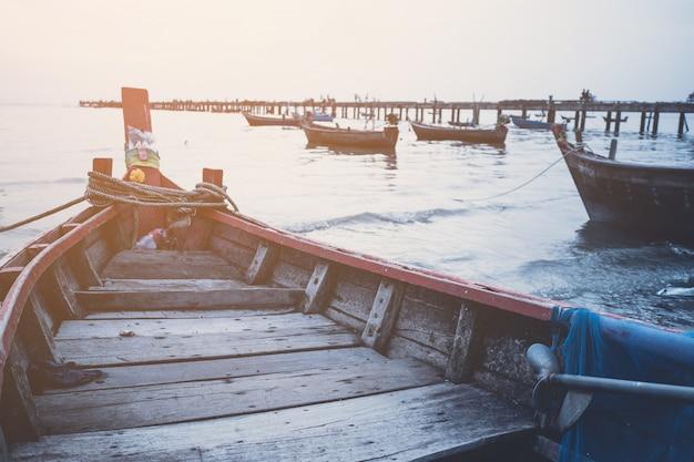 Barco de pesca local e o pôr do sol do mar