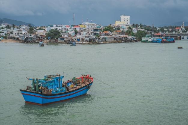 Barco de pesca na âncora fora da vila pobre em nha trang