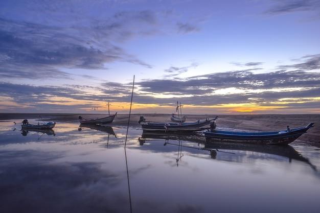 Barco de pesca na costa de mar com luz da manhã, reflexão do céu e nuvens no mar.
