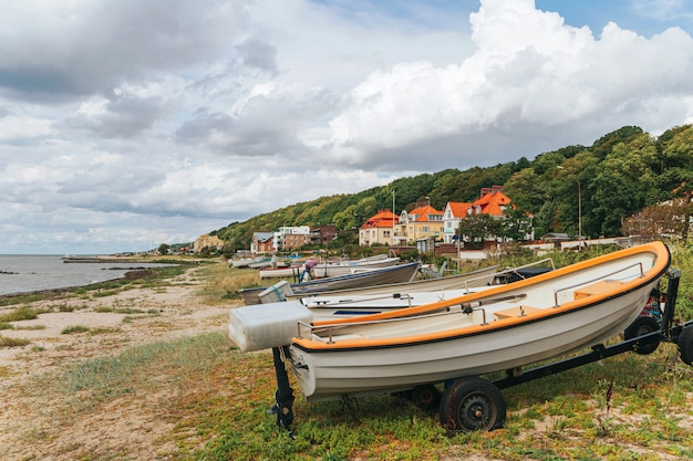 Barco de pesca na praia, barco na costa do mar, barco a remo velho na praia.