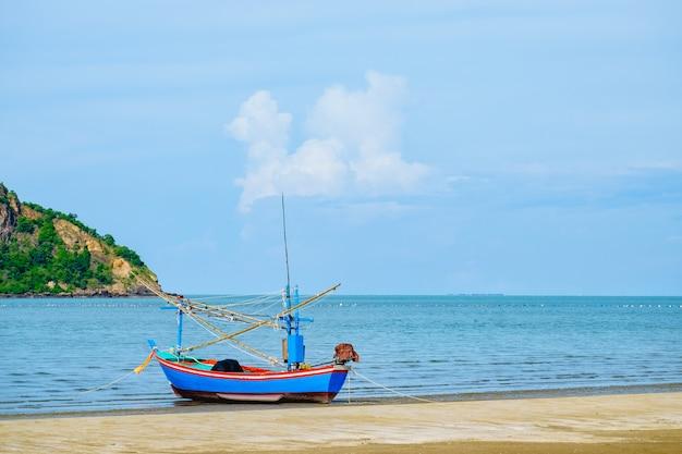 Barco de pesca na praia com céu azul e mar.