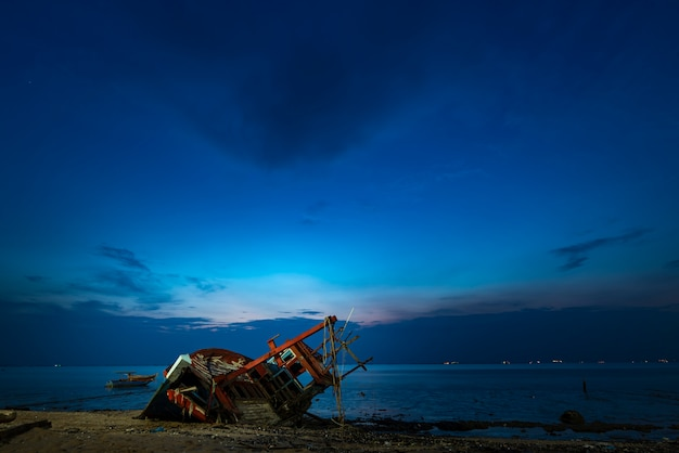 Barco de pesca naufrágio na praia, pôr do sol