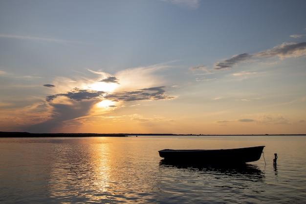Barco de pesca no lago ao pôr do sol.