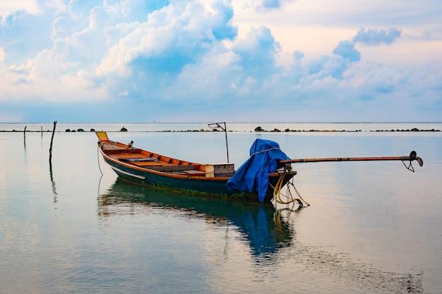 Barco de pesca no mar, pôr do sol e silhuetas de barcos de madeira