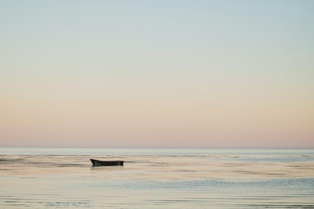 Barco de pesca pequena na baía ao pôr do sol ao entardecer