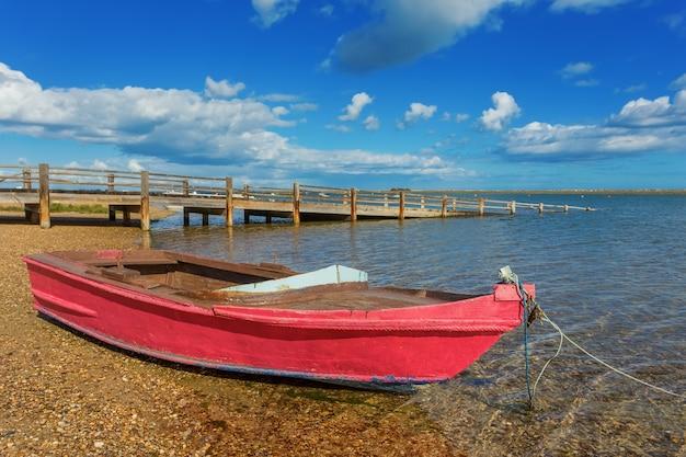 Barco de pesca vermelho na praia. perto da ponte.