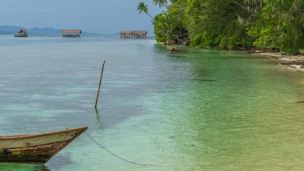Barco de pescador perto da estação de mergulho e pousadas na ilha de kri, raja ampat, indonésia, papua ocidental.