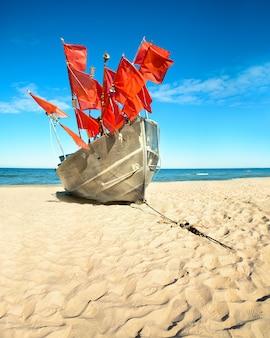 Barco de pescador tradicional em uma costa arenosa do mar báltico