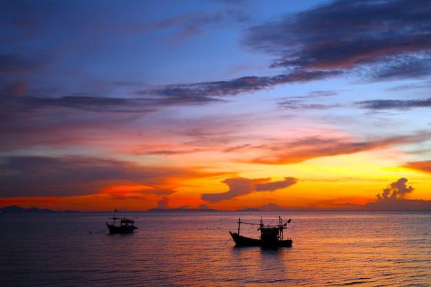 Barco de silhueta no mar e pôr do sol colorido