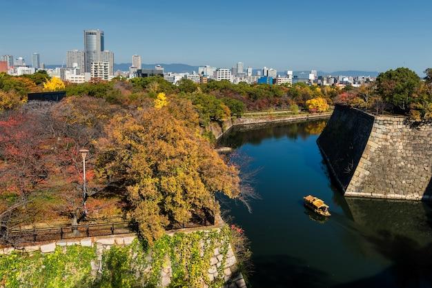Barco de torist no castelo de osaka com árvores de outono