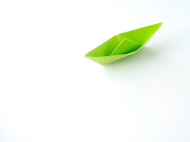 Barco do papel verde colocado no fundo branco.