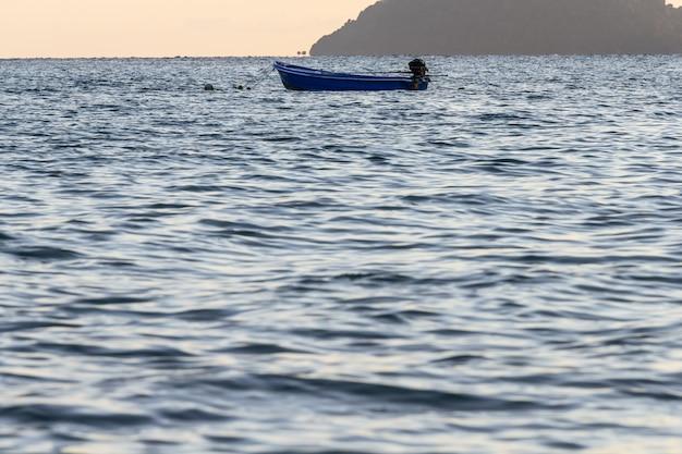 Barco do pescador que flutua sobre a superfície da onda do mar que reflete com cor azul, amarela do céu.