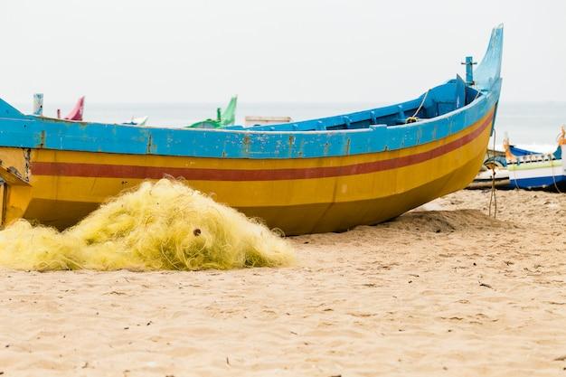 Barco e redes coloridos da pesca na praia em um dia nebuloso.