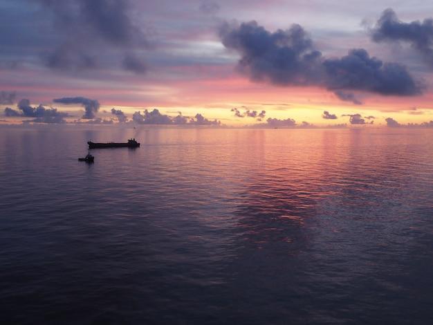 Barco em um mar sob um céu nublado durante um belo pôr do sol colorido à noite