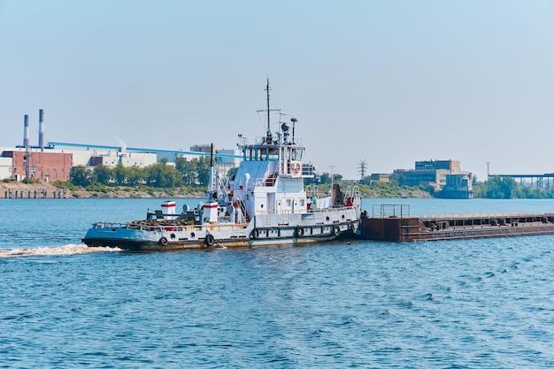Barco empurrador empurra barcaça de carga a granel no rio em uma paisagem industrial