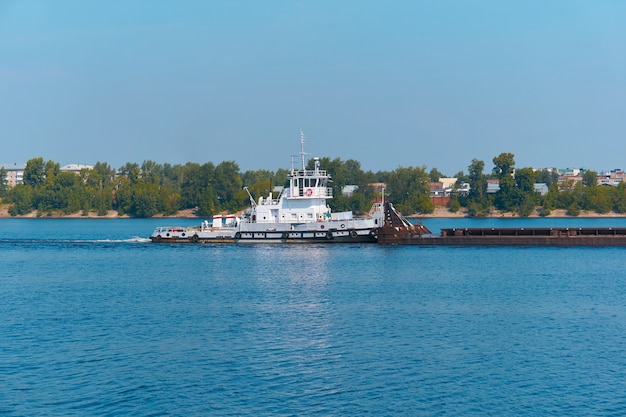 Barco empurrador empurra barcaça de carga a granel no rio, passando pela costa da cidade