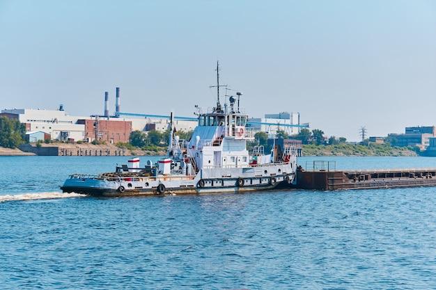 Barco empurrador empurra barcaça de carga a granel no rio, passando pela paisagem industrial