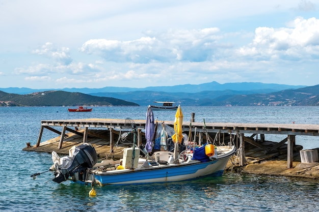 Barco encalhado de metal motorizado colorido em um píer na costa do mar egeu, colinas e uma cidade em ouranoupolis, grécia