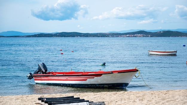Barco encalhado de metal motorizado colorido na costa do mar egeu, colinas e uma cidade em ouranoupolis, grécia