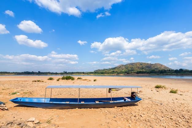 Barco estacionado no chão de areia seca do rio mae khong com vista para a montanha do laos nas corredeiras de kaeng khud khu em chiang khan