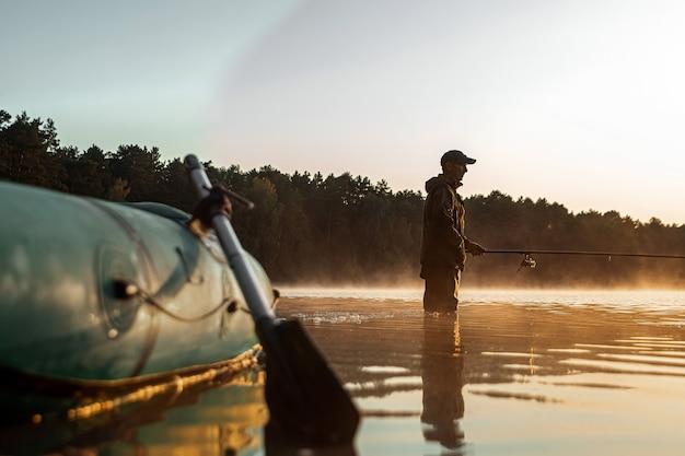 Barco inflável no lago ao amanhecer, um pescador ao amanhecer pesca férias de hobby de pesca
