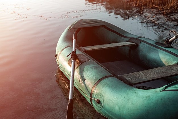 Barco inflável no lago ao nascer do sol