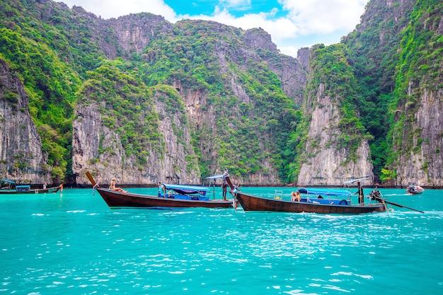Barco longo e água azul na baía de maya na ilha phi phi, krabi tailândia.