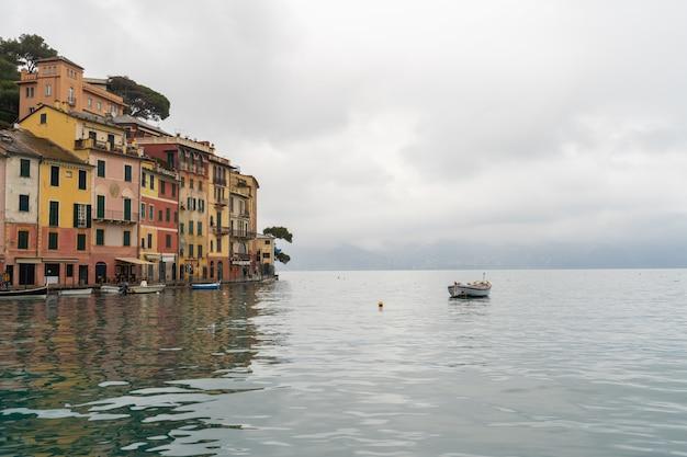 Barco na água com casas coloridas na praça de portofino.