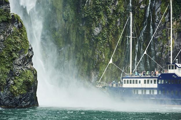 Barco navega pelo fiorde se aproximando de uma cachoeira em milford sound, nova zelândia