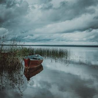 Barco no lago com uma reflexão árvores e celeiro