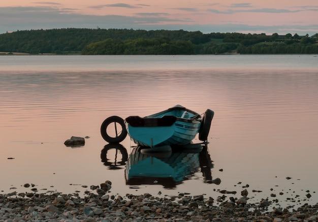 Barco no lago perto da cidade de mullingar, na irlanda, com reflexo na água ao pôr do sol