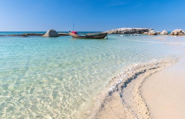 Barco no mar azul e praia de areia branca.