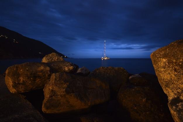 Barco no mar com uma moldura de pedras